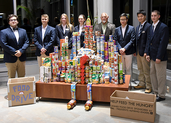 students wearing blue suite coats in front of cans of food