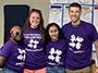 four students wearing purple shirts