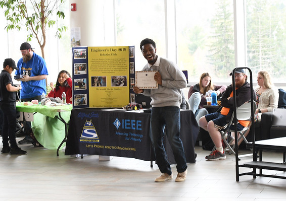 student holding a certificate in front of a poster board on a table