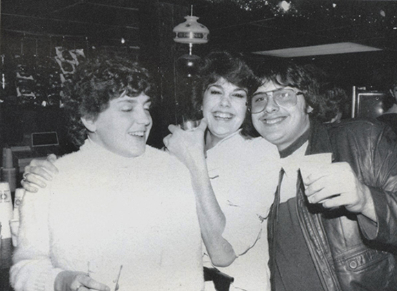 three students gather at Pioneer Pub in 1985 holding drinks