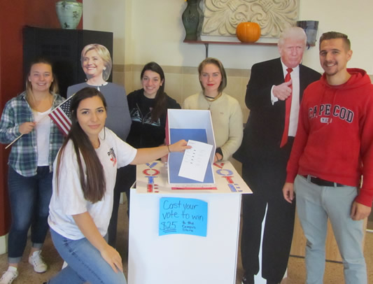 students standing next to cardboard cut outs of Donald Trump and Hillary Clinton
