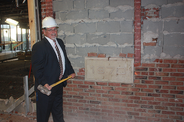 President Dr. Skip Sullivan at the MacKenzie Complex wearing a hard helmet and holding a hammer