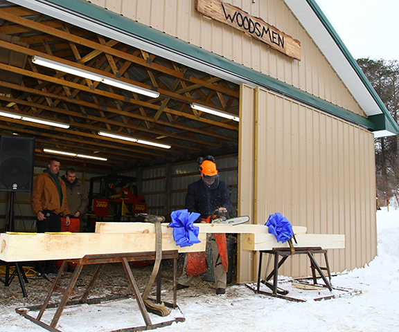 "Alfred State President Dr. Skip Sullivan uses a chainsaw Wednesday to cut the wooden ""ribbon"" at a ceremony to celebrate the new Pioneer Woodsmen's Club Barn."