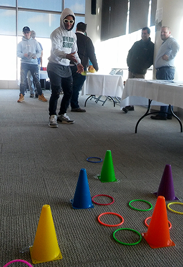 student tossing rings onto colorful cones