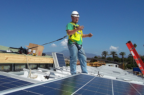 Ryan Kozlowski, an Alfred State electrical construction and maintenance electrician major from Buffalo, is surrounded by solar panels on the top of Team Alfred's entry in the 2015 US Department of Energy Solar Decathlon