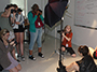 students in the photography class of the NYSSSA School of Media Arts, holding cameras and a light shining on students