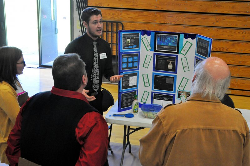 male student explaining his poster