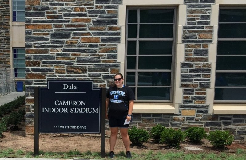 student standing in front of a sign at Duke University