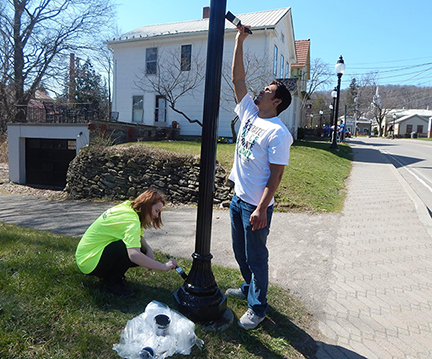 Juliana Krajewski and Abraham Kalamadeen paint a Victorian street light pole on Main Street