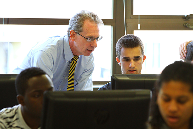 Associate Professor of Business Steven Reynolds provides assistance to a student on a computer in a lab.