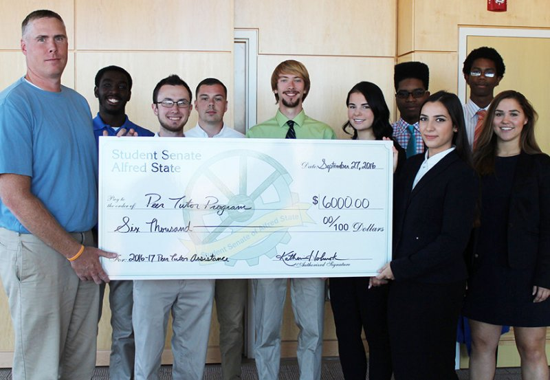 Student Senate members present a check to the peer tutoring coordinator
