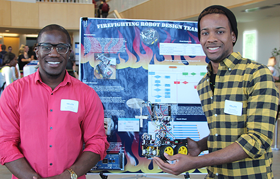 two male students holding their electrical engineering project, standing in front of a poster presentation