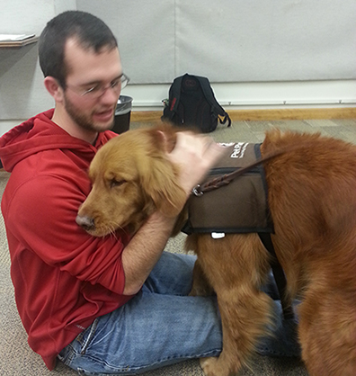 male student with a therapy dog