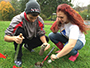 Two students take a sample of soil to analyze
