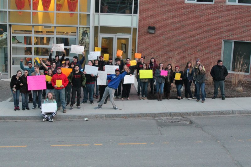 students in front of the SLC building holding up posters