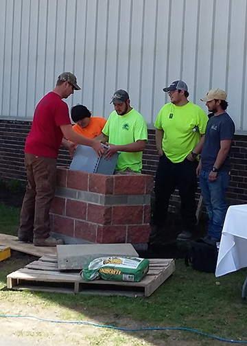 Wellsville students lower the time capsule into its spot