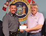 Lt. Scott Bingham presents Rod Ballengee a check