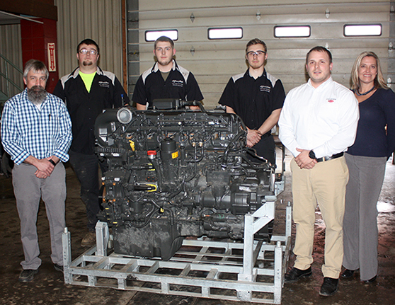 six people standing around a large engine