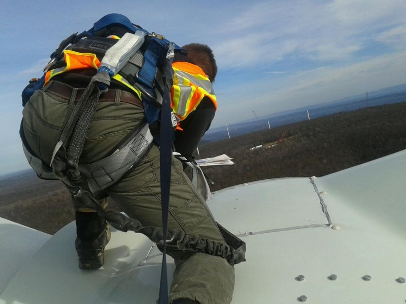 Alfred State grad - top of the hub -windmill, back view of grad wearing safety harness