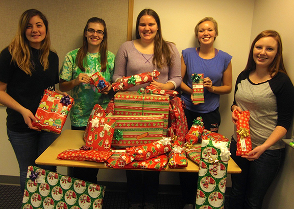students in WINS club with holiday presents that they wrapped
