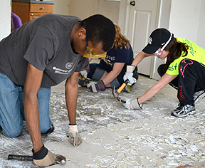 students scraping a floor during spring break