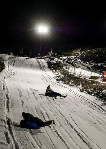 Two students tubing down the new tubing hill