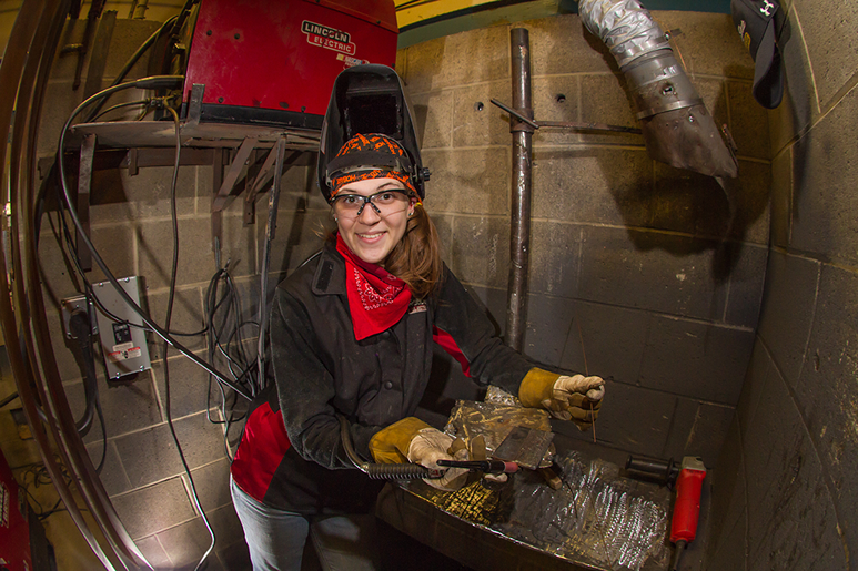 Emily Slayton wearing a welding hat and protective gear