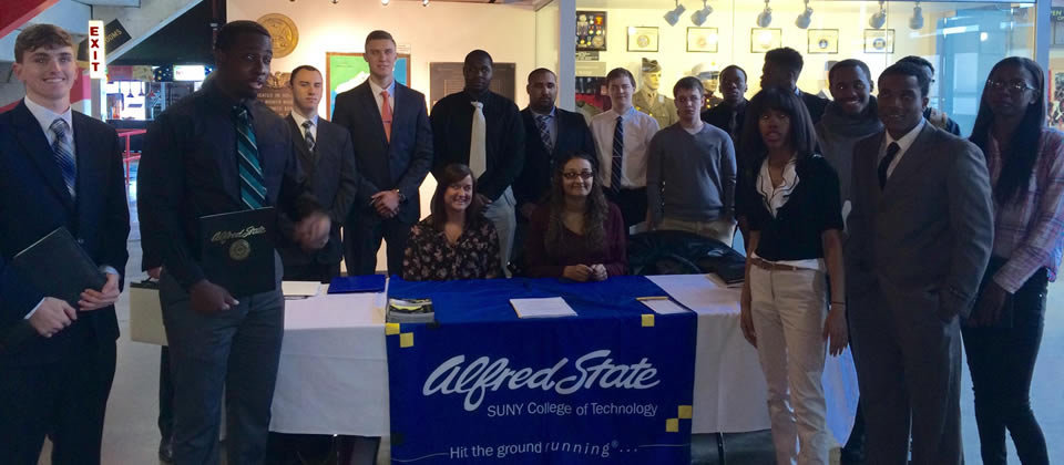 several students standing around a table with an Alfred State banner