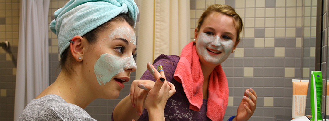 2 female students in a bathroom applying a face mask in front of the mirror