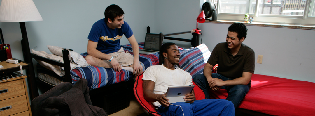 3 male students sitting on beds in a dorm room