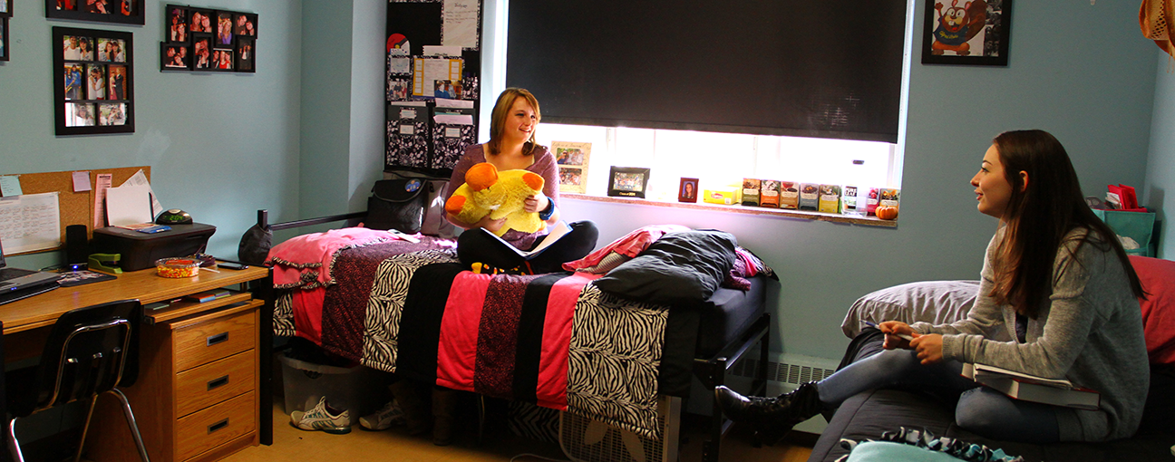 2 female students sitting on beds in a dorm room