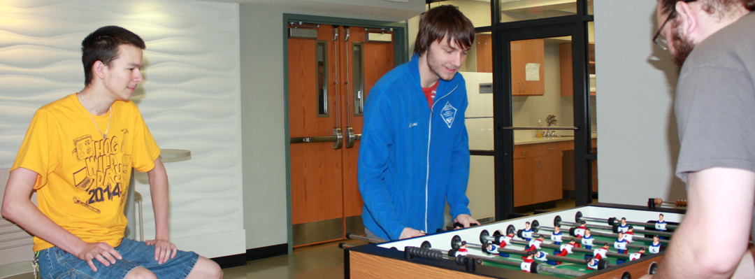 2 male students playing a game in residential hall lounge