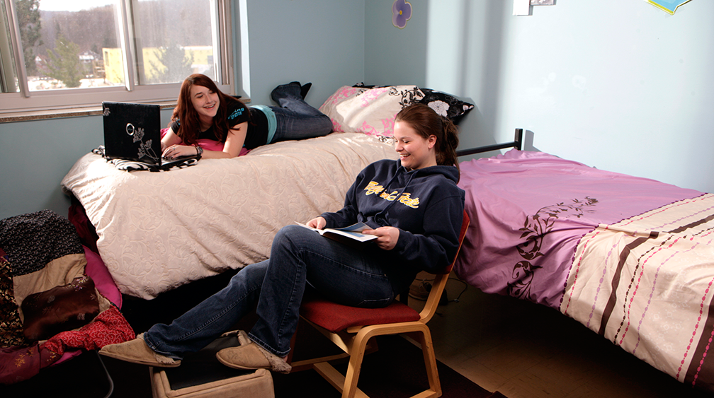 2 female students in a residence hall, one is laying on a bed and the other is sitting in a chair