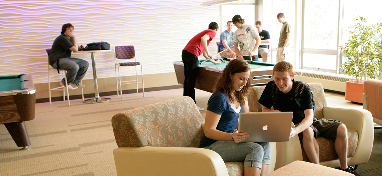 several students in residence hall lounge playing games and looking at a computer