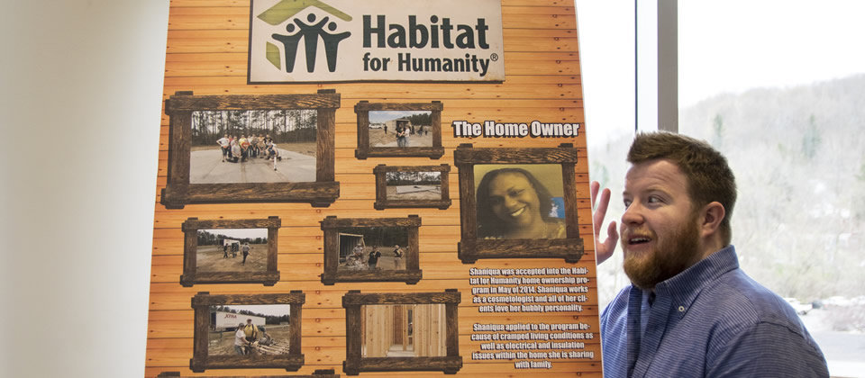 student presenting a poster board about Habitat for Humanity