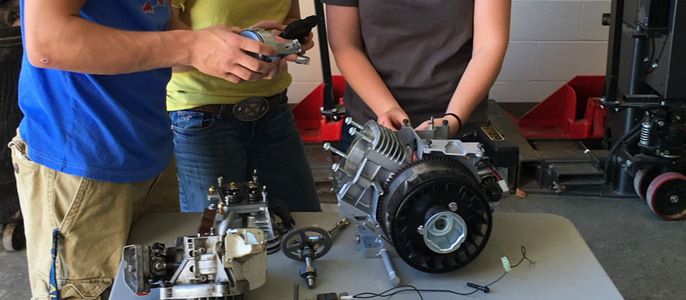2 students around a table with some motor parts