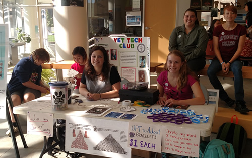 students sitting at a table selling items for a fundraiser