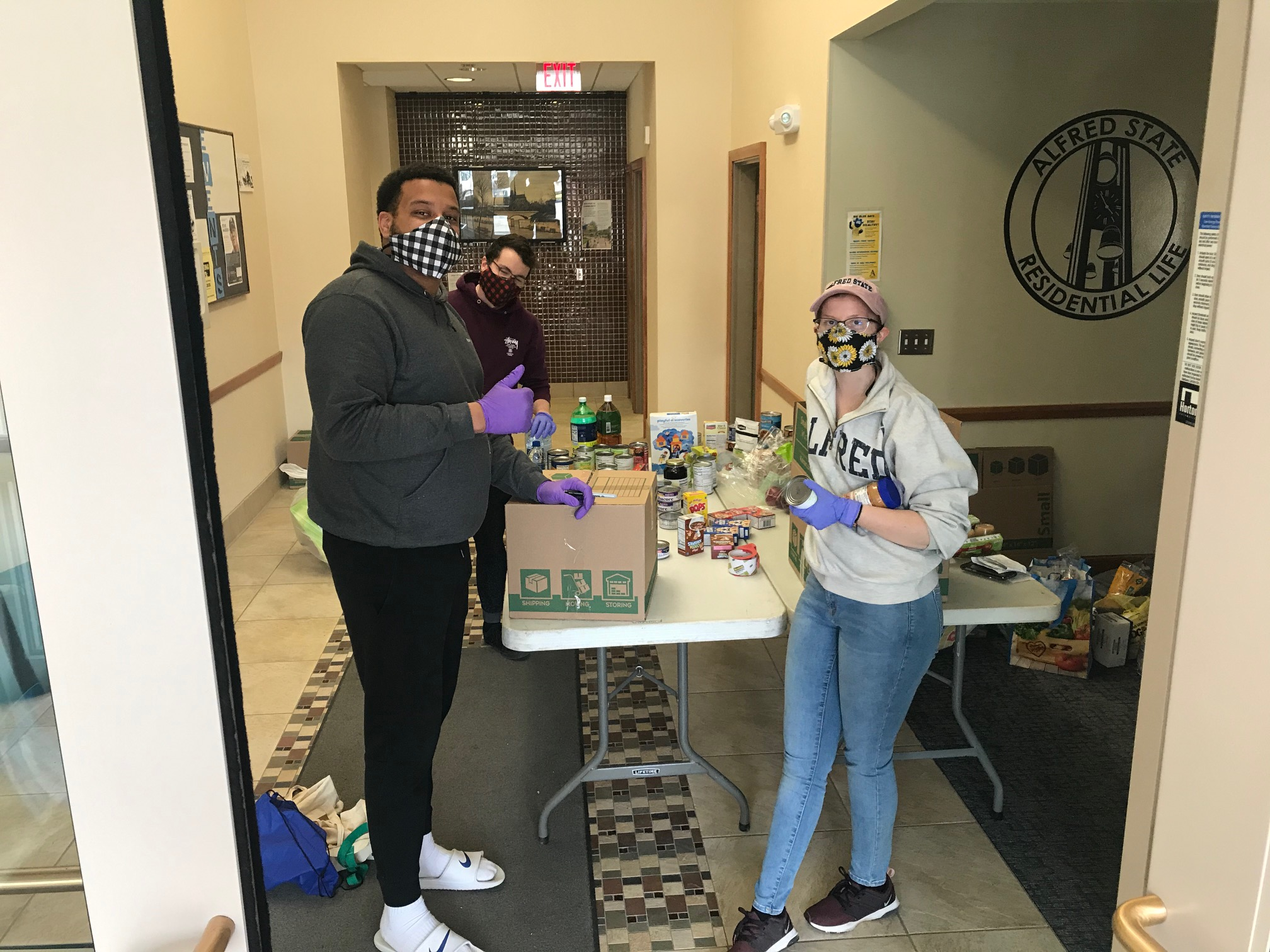Alfred State staff members help a student through the new pilot food pantry program