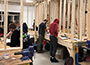 students in a carpentry lab, pieces of lumber
