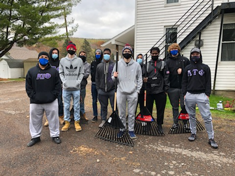 Brothers of Lambda Tau Phi outside with rakes