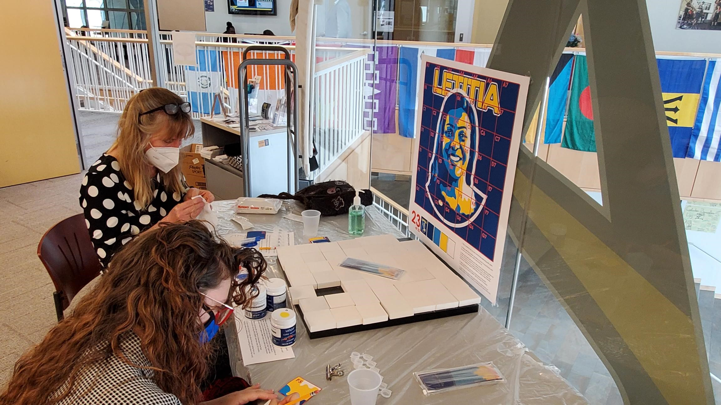 Provost Kristin Poppo and student Molly Lockwood prepare to paint segments of a mural of Letitia James.