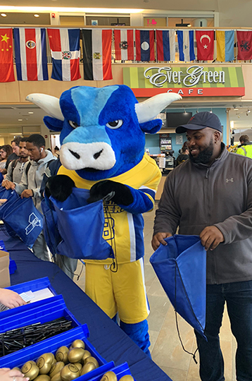 ox mascot and male holding blue bags open in SLC