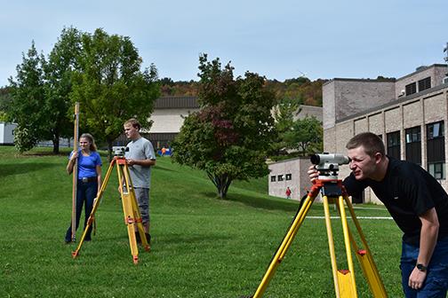 three surveying students using equipment outside