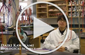 student sitting in a lab with a white lab coat on, link to youtube video