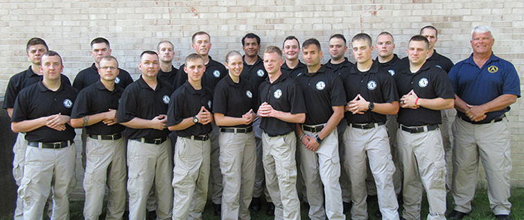 students in the police academy standing with their instructor