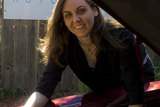 Kate Jonasse standing next to a car, underneath the hood