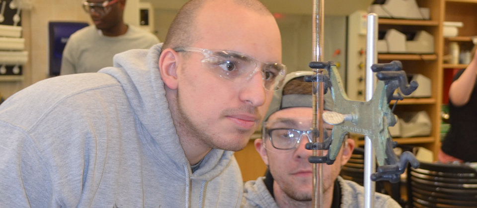 2 male students looking at water in a lab