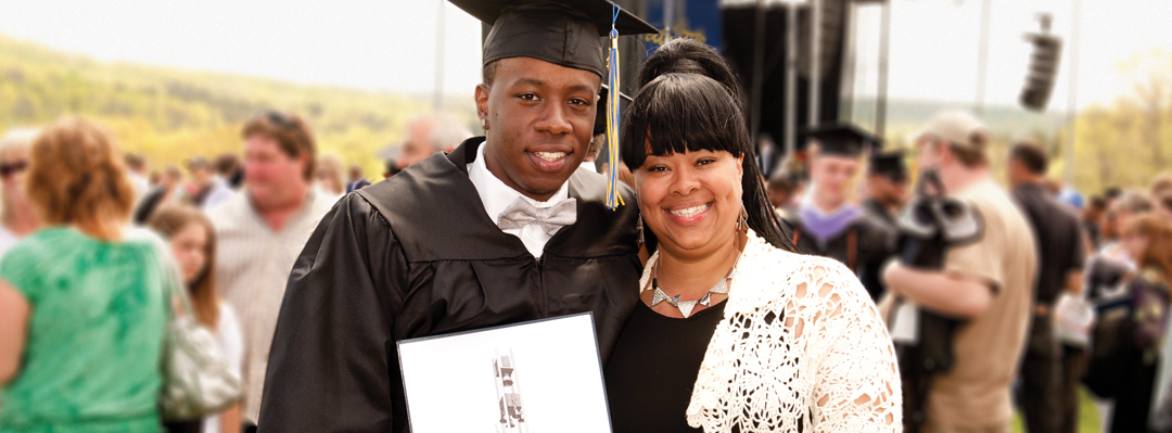 male student wearing commencement cap and gown holding his diploma, with mother