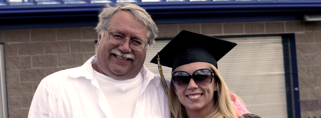 father and daughter, daughter wearing commencement cap and sunglasses