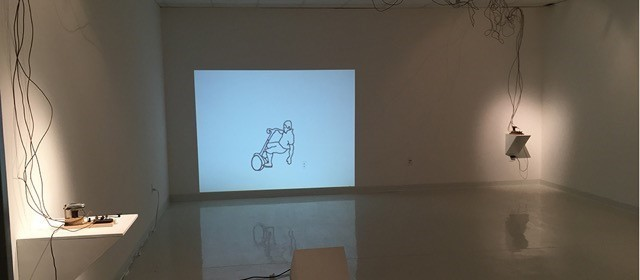 empty room with a drawing on the wall of someone on a segway, wires hanging down on the walls
